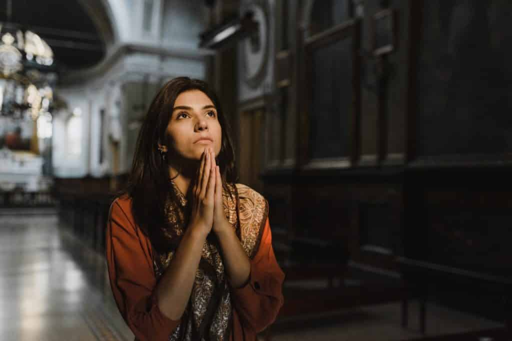 Mulher branca com as mãos juntas na igreja.