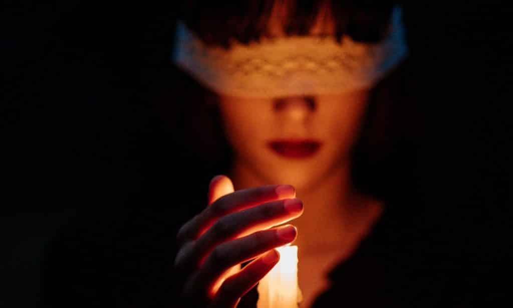 Mulher com os olhos vendados segura vela acesa.