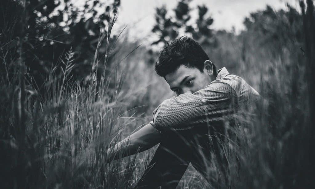 Imagem monocromática de homem sentado na grama. Seu rosto está sob o braço, que repousa sobre os próprios joelhos.