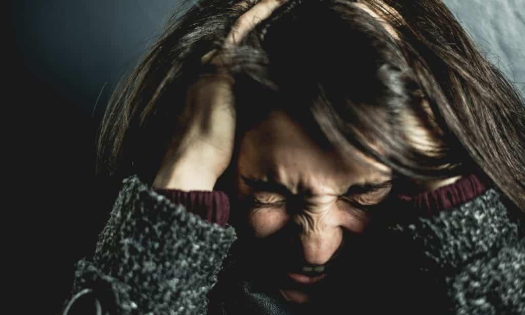 Mulher pressiona a cabeça entre as próprias mãos. Seu semblante está aflito, com o cenho franzido.