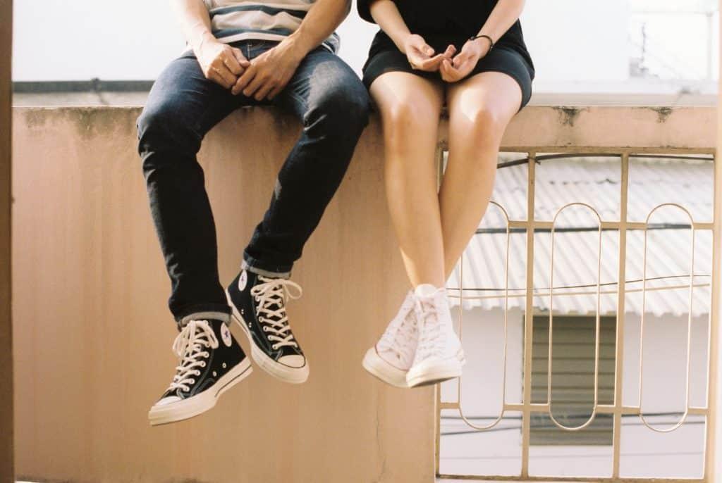 Homem e mulher sentados em um muro