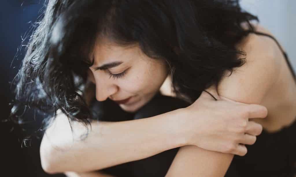 Mulher agachada com o corpo apoiado nas pernas. Ela abraça os próprios braços e tem um semblante aflito, além de estar cabisbaixa.