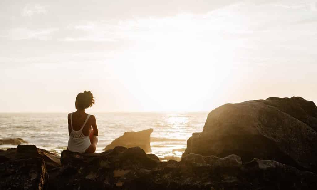 Mulher sentada sobre pedras observa o mar.