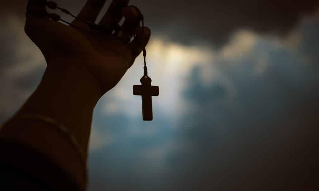 Terço sobre mão erguida em direção ao céu.