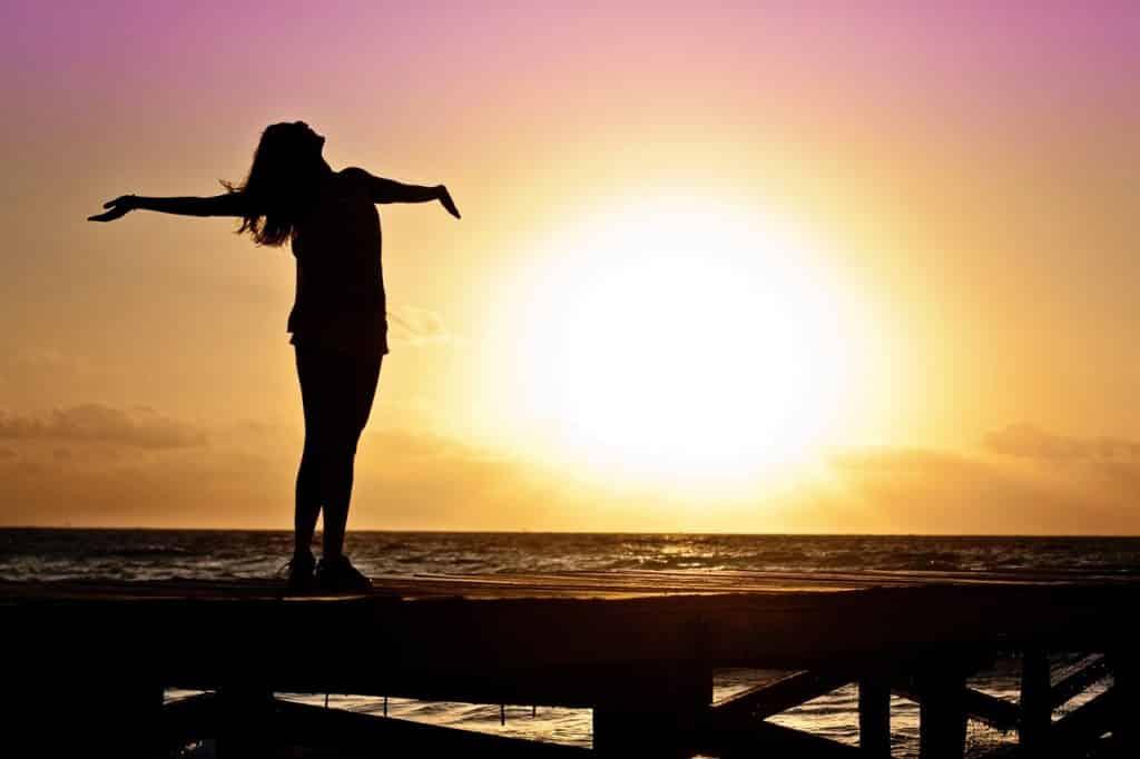 Mulher com os braços abertos com um pôr-do-sol de fundo.