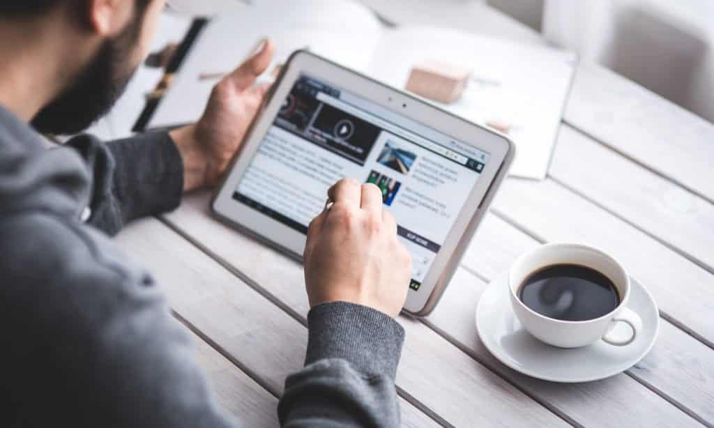 Homem lê site de notícias em tablet. Ele está sentado à mesa e, sobre ela, há uma xícara de café.