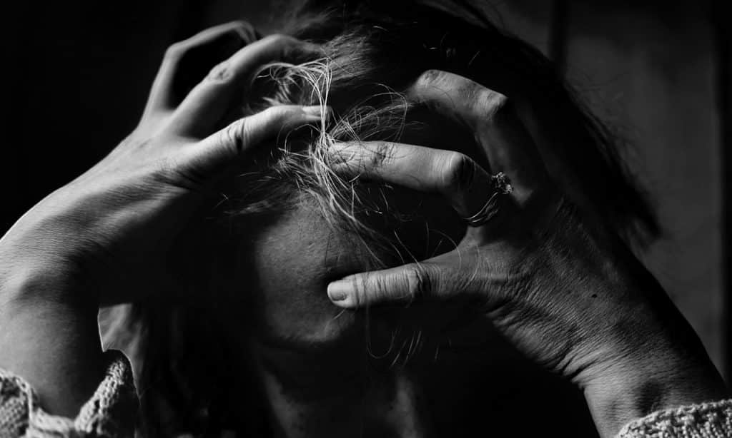 Mulher pressiona os dedos contra a própria cabeça. Ela está cabisbaixa.