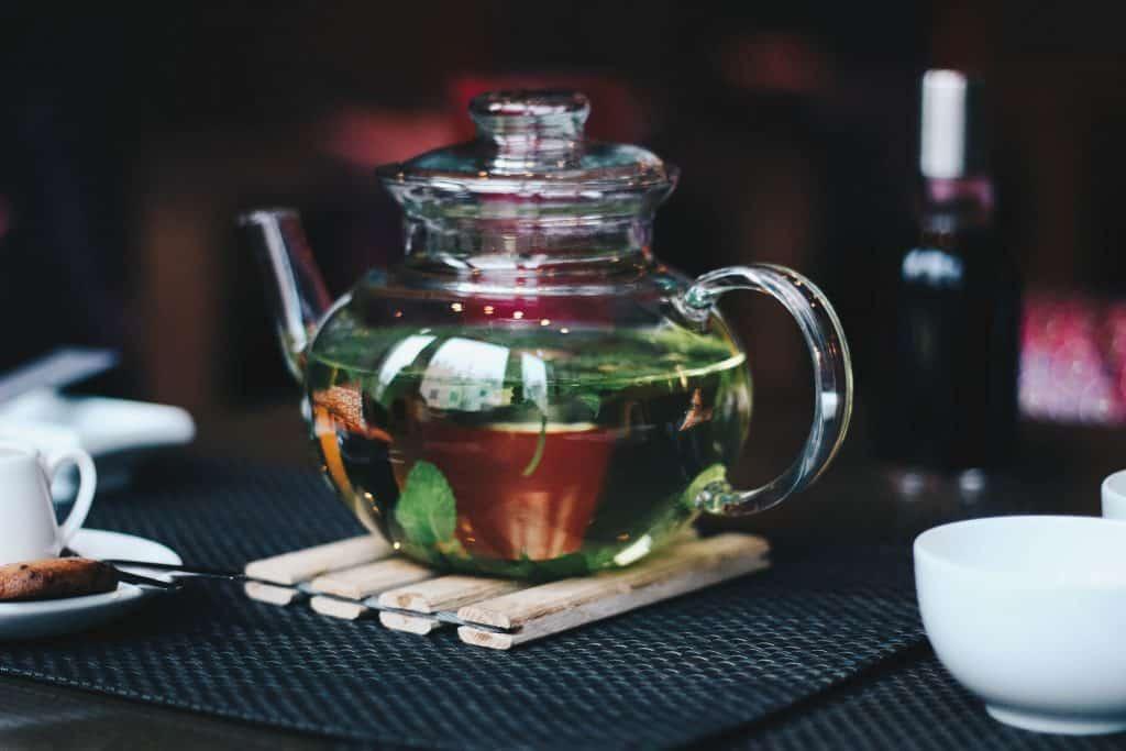 Jarra de chá de vidro com várias ervas dentro