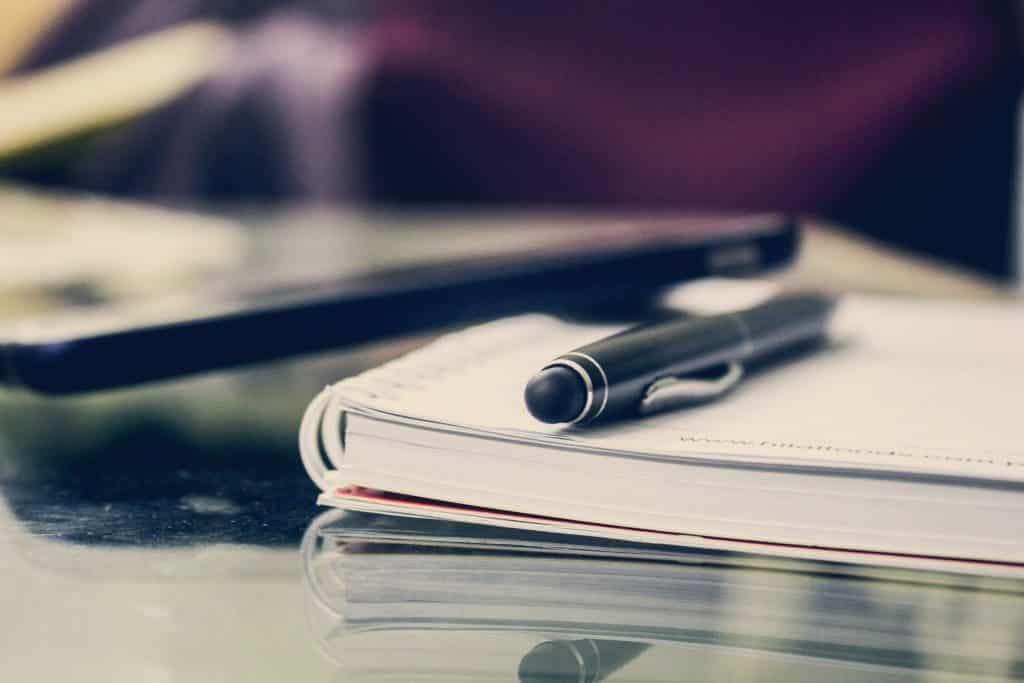 Caderno em uma mesa com uma caneta