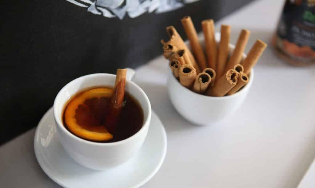 Chá de canela servido em xícara de porcelana branca. Ao lado, em recipiente do mesmo material, há canelas em casca.