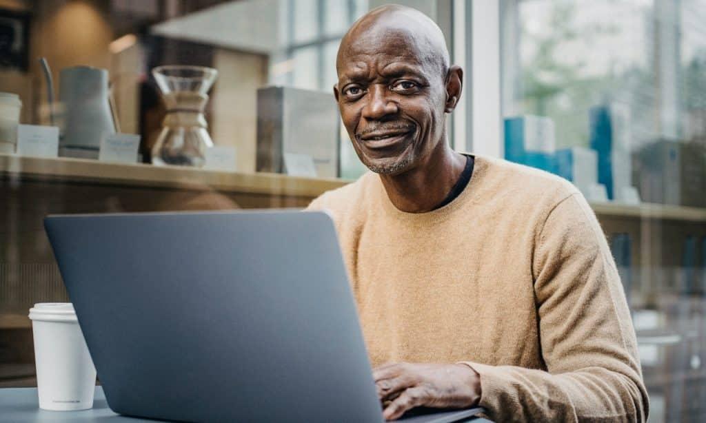 Homem sentado à mesa mexe em computador.