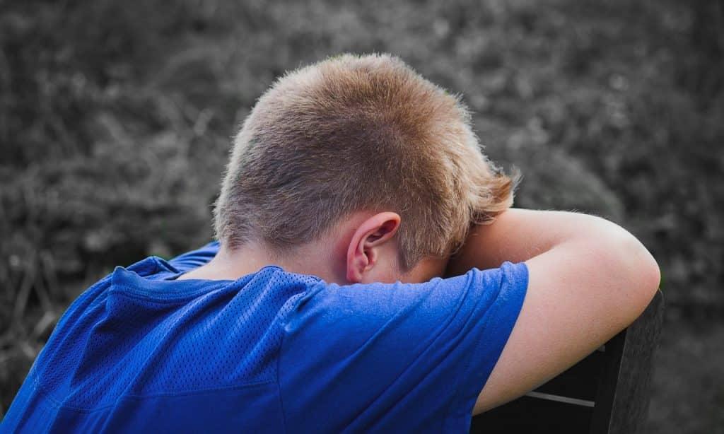Menino esconde o rosto sob o próprio braço.