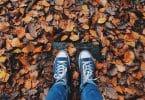 Pessoa usando tênis com folhas caídas no chão
