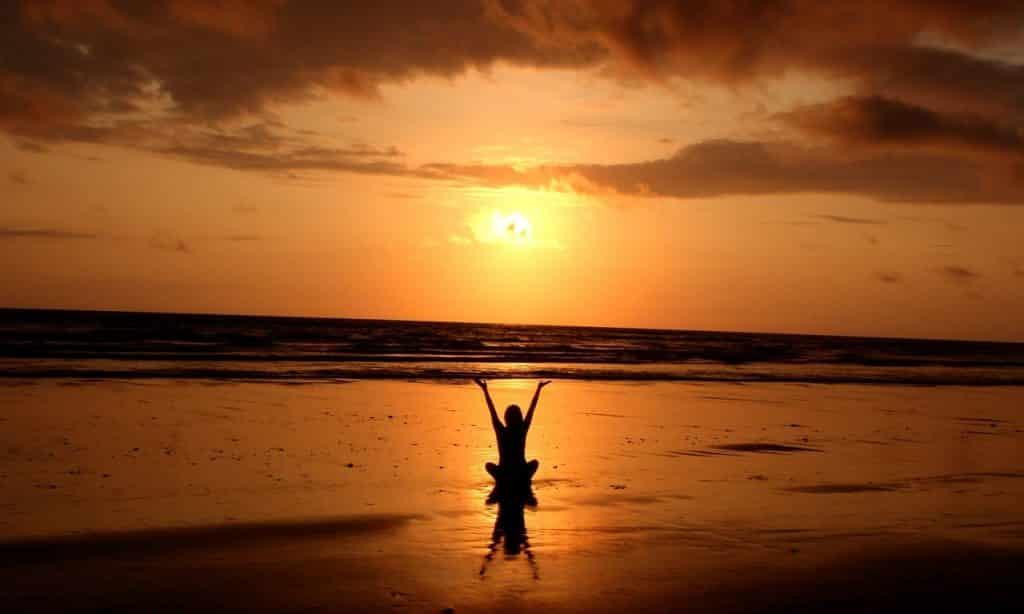 Silhueta de mulher com os braços erguidos. Ela está na praia e assiste ao pôr do sol.