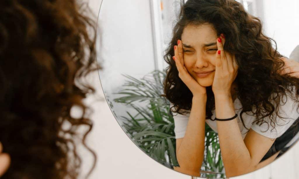 Mulher observa seu próprio reflexo no espelho. Seu semblante é aflito.