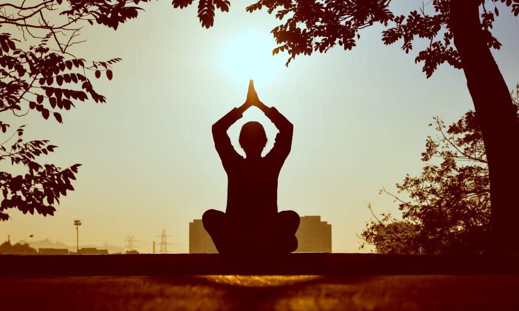 Um pessoa sentada no chão de uma praça meditando em frente ao Sol.