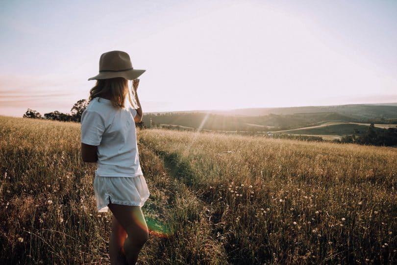 Mulher em um gramado olhando para o sol