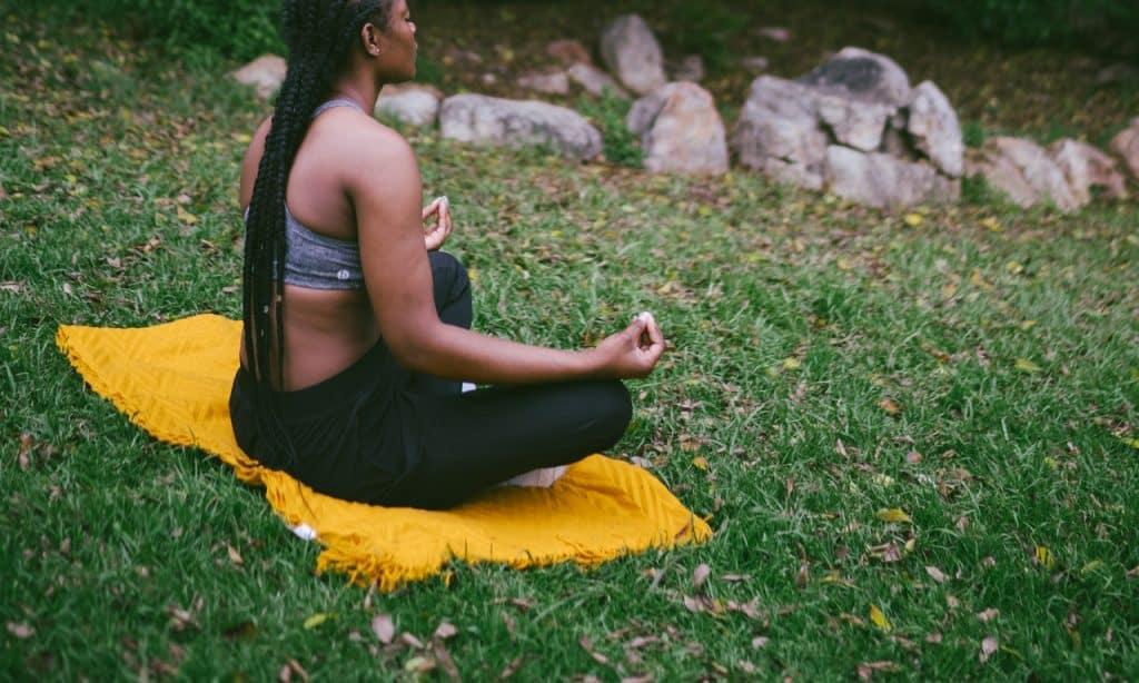 Mulher sentada em tecido amarelo sobre grama. Ela está em exercício meditativo.