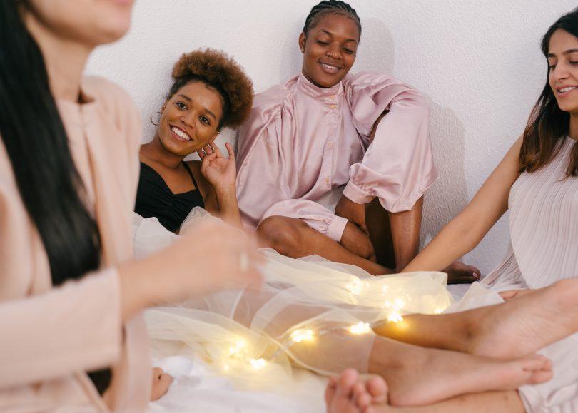 Mulheres sentadas uma ao lado da outra sorrindo