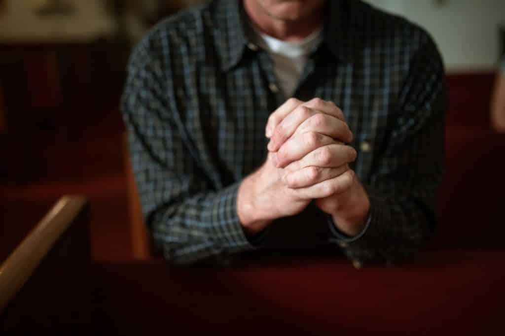 Homem branco com as mãos juntas rezando.