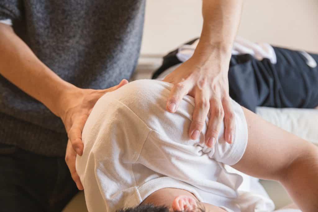 Pessoa recebendo massagem no ombro.