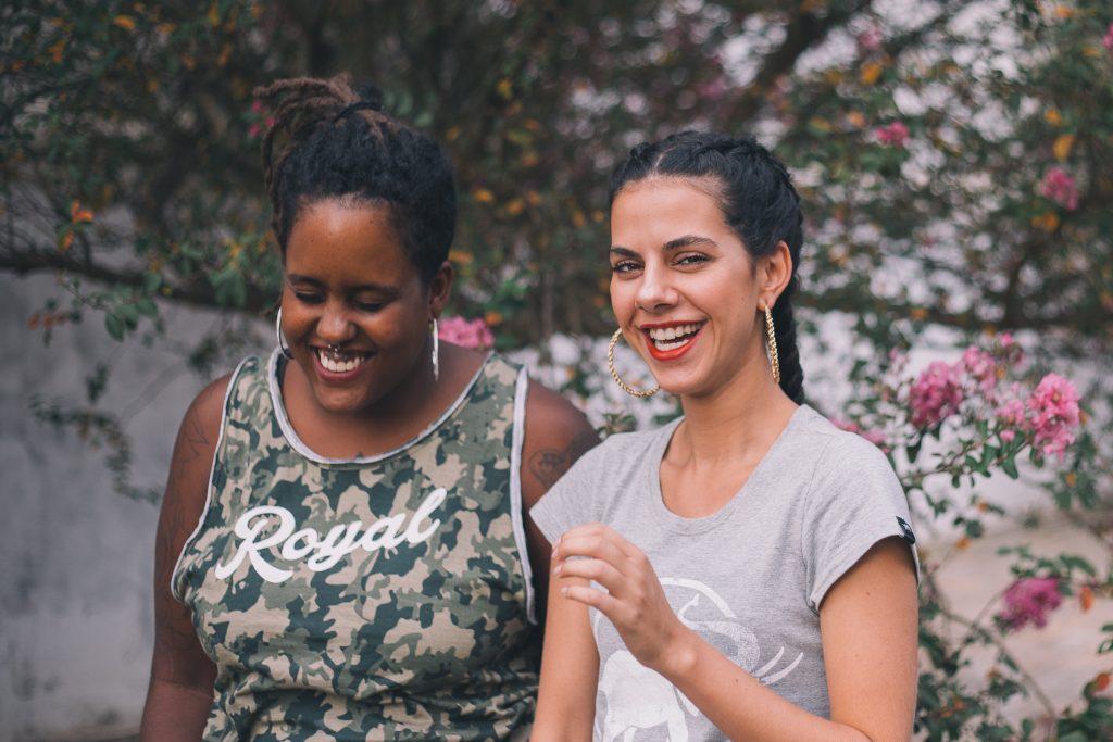 Duas mulheres sorrindo uma ao lado da outra