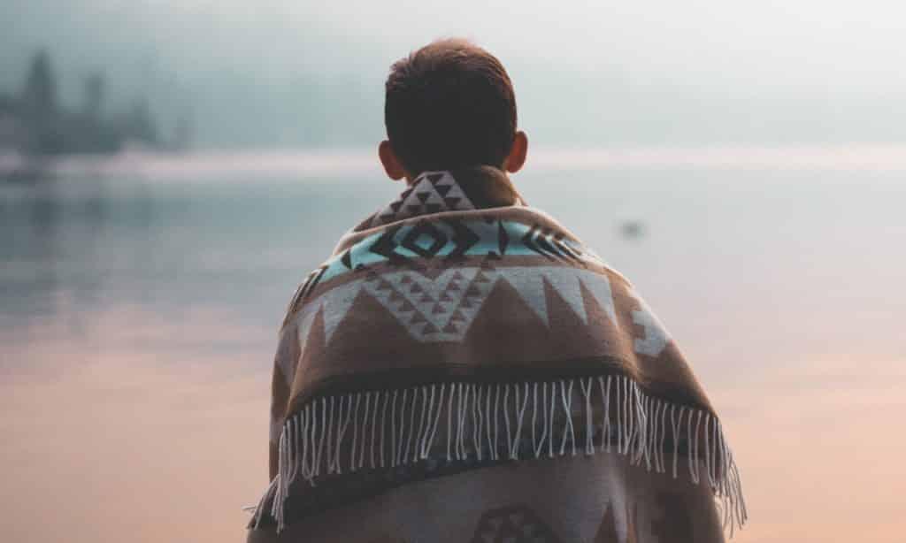 Homem sentado com o corpo coberto por tecido estampado. Ele observa o horizonte.