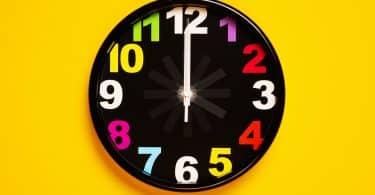 Relógio de parede com números coloridos e plano de fundo amarelo