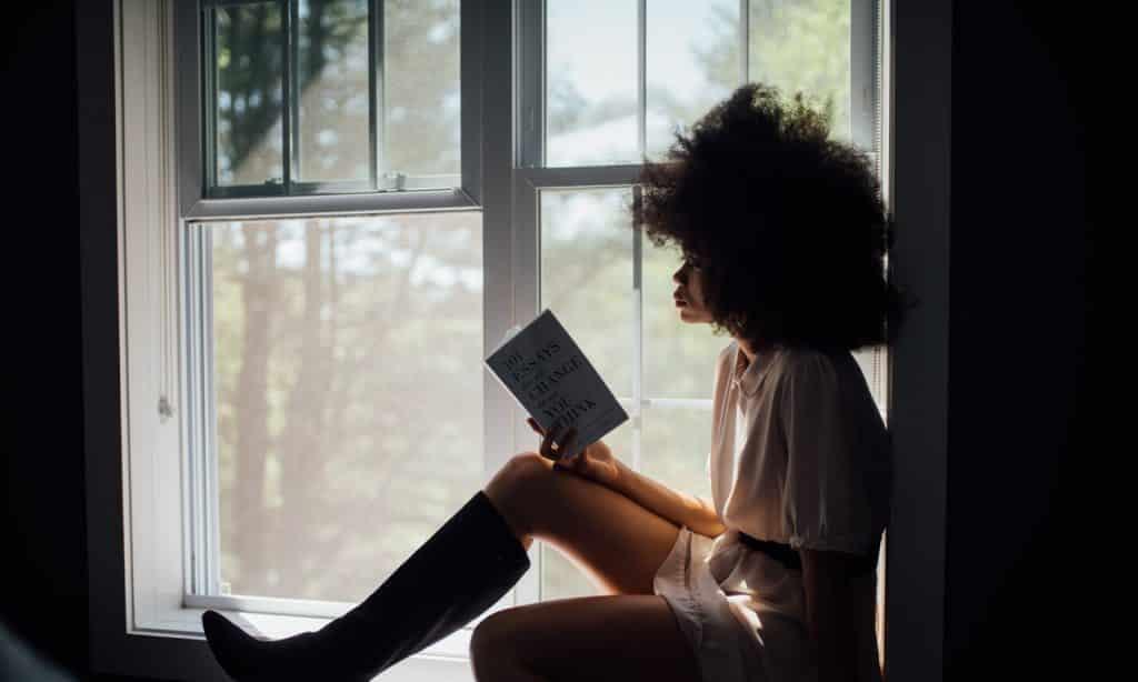 Mulher sentada à janela lê um livro.