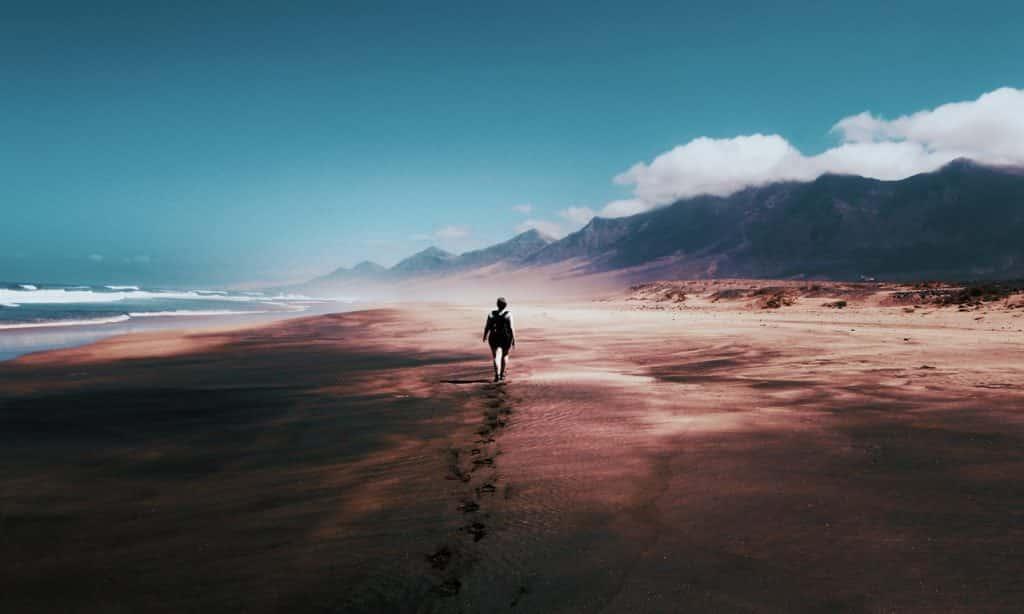 Homem anda na areia em direção às montanhas.