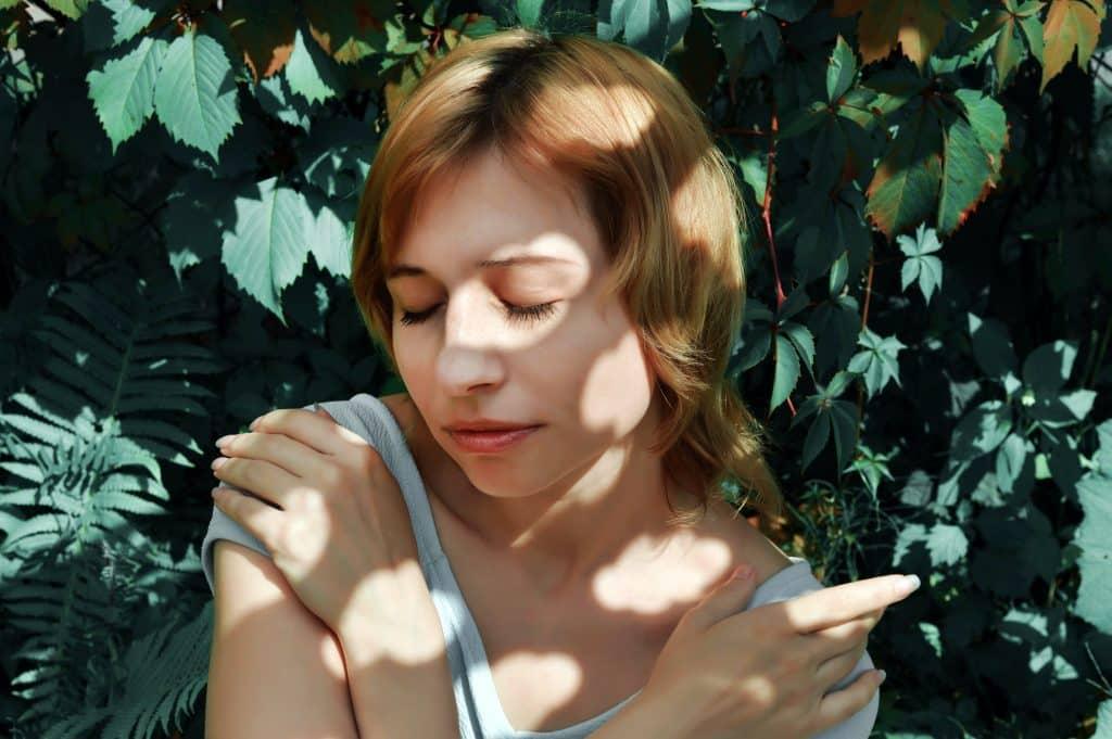 Mulher de olhos fechados com seus braços juntos ao lado de plantas