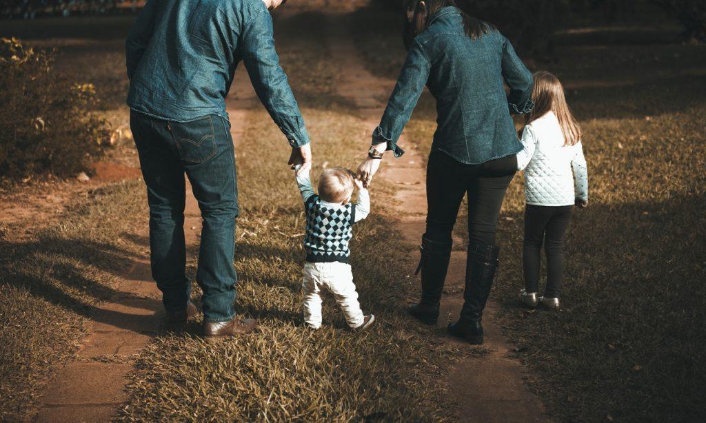 Família composta por duas crianças e dois adultos caminha em ambiente externo.