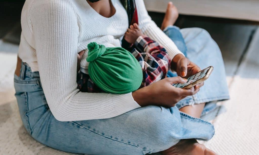 Mulher amamenta criança enquanto mexe em celular.
