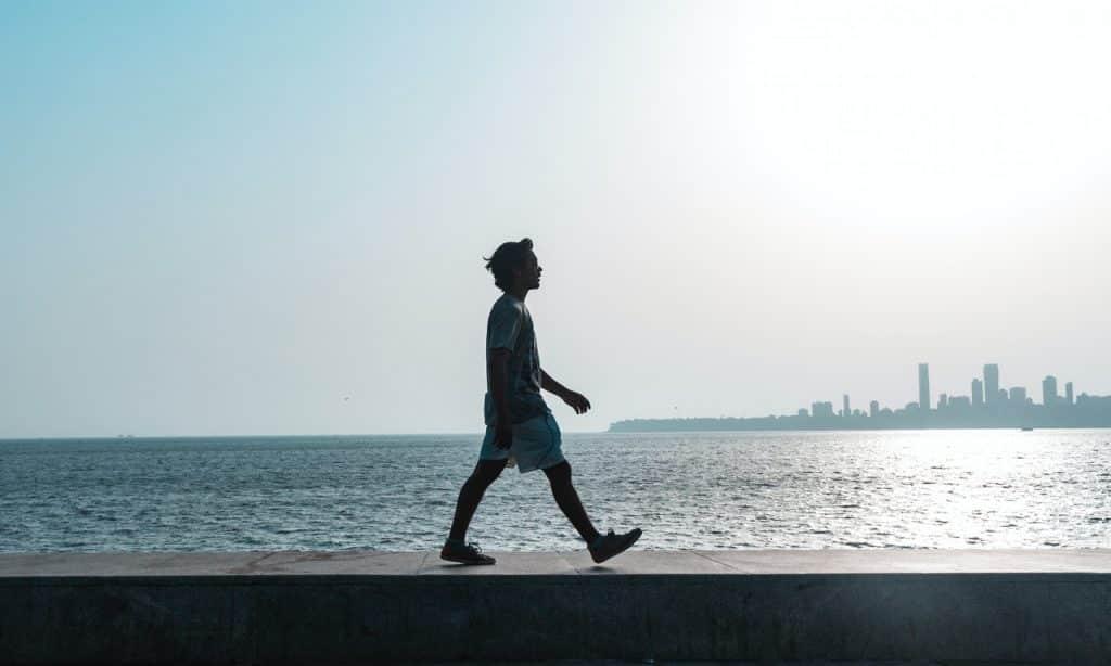 Homem andando à beira de um lago.