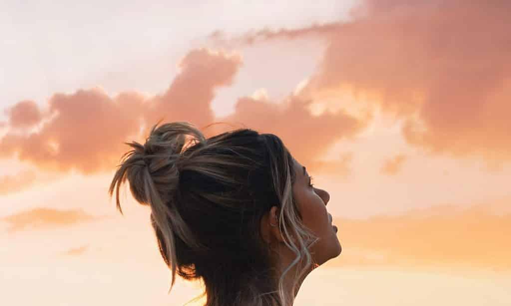 Mulher observa céu alaranjado com nuvens aparentes.