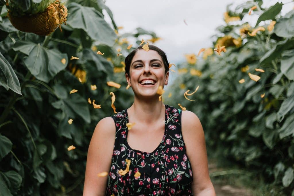 Mulher branca sorrindo em meio a plantas.