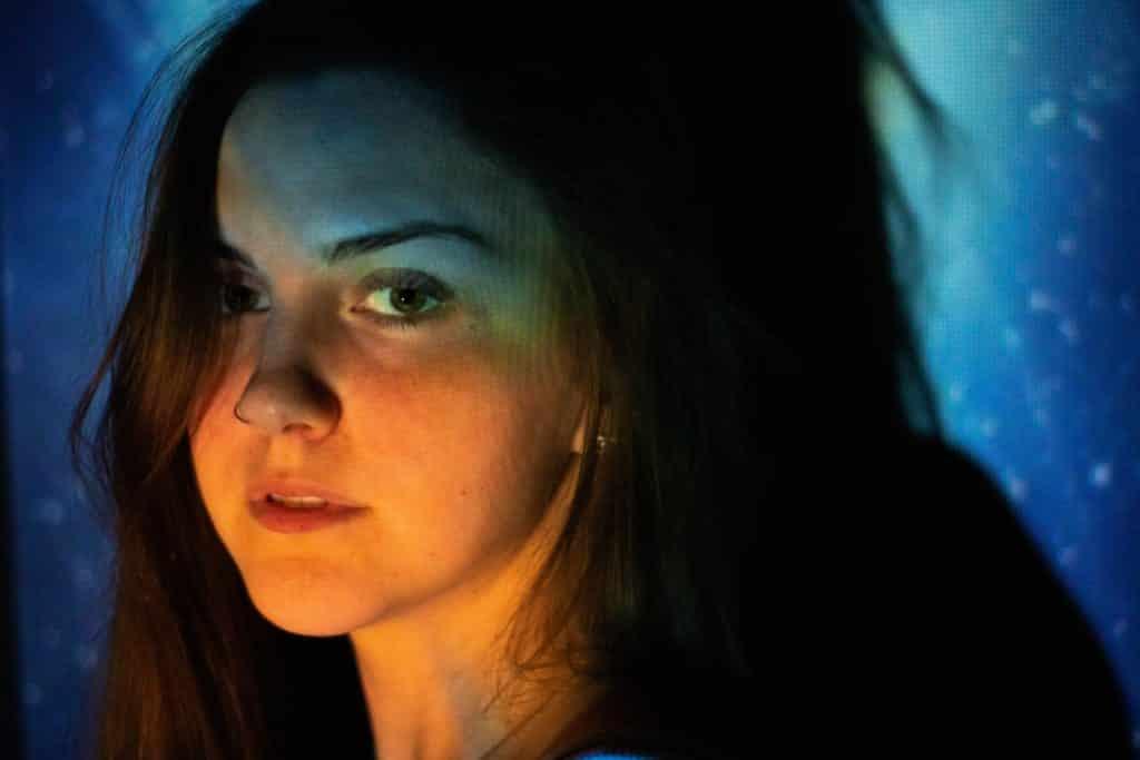 Mulher branca iluminada por luzes coloridas.