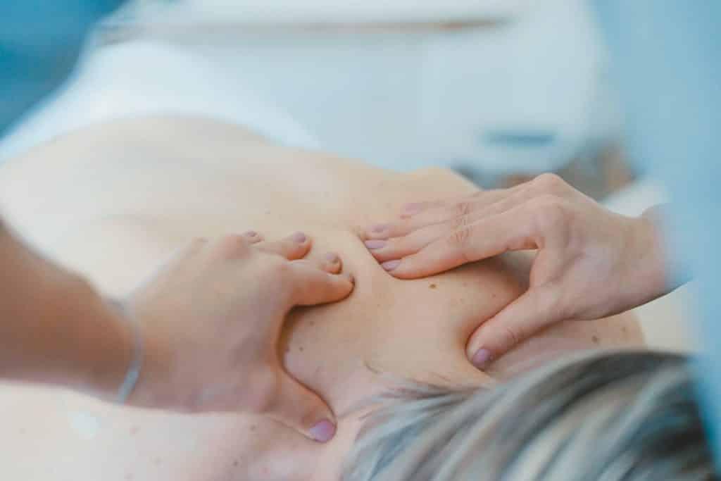 Pessoa branca recebendo massagem nas costas.