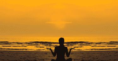 Pessoa meditando na praia durante o pôr do sol