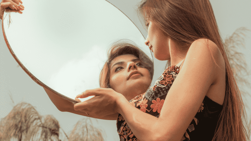 Mulher segurando um espelho vendo o seu próprio reflexo