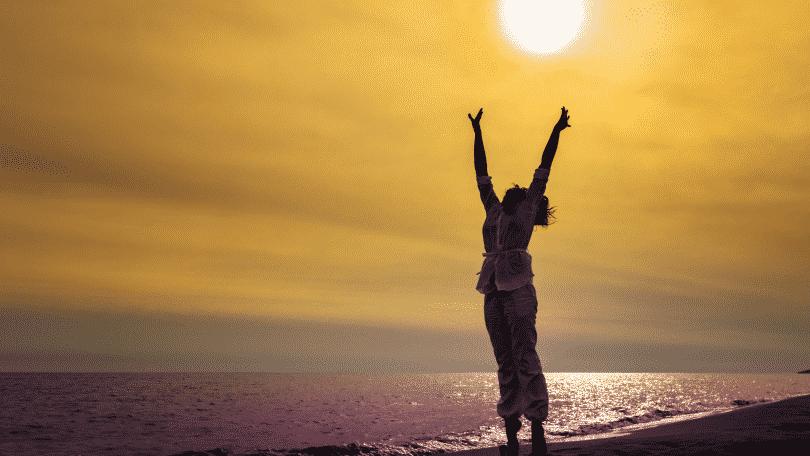 Mulher na praia com os braços erguidos para o sol