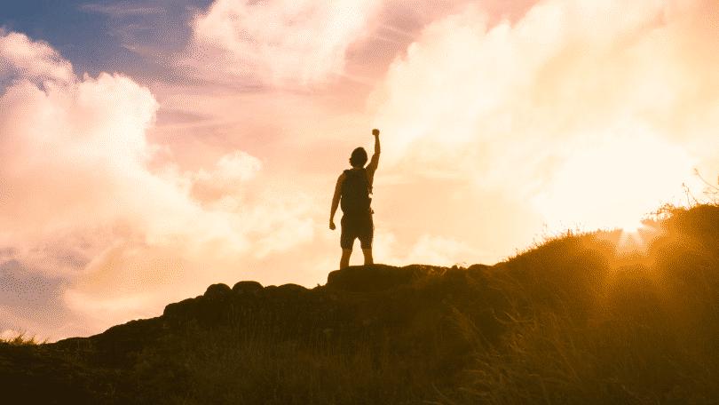 Homem com o braço erguido no topo da montanha