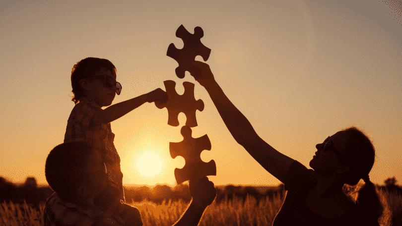 Família montando quebra-cabeça juntos durante pôr do sol