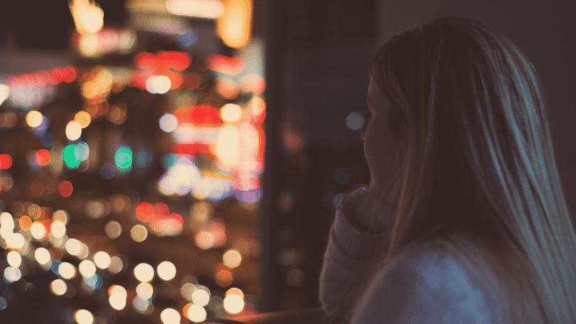Mulher observando a cidade pela janela