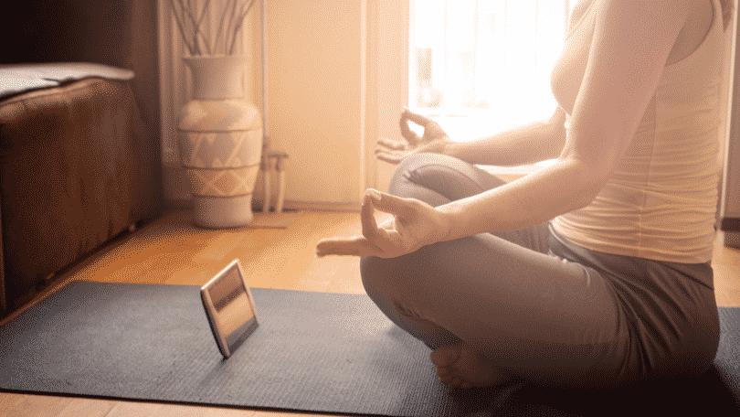 Mulher meditando na sala de estar