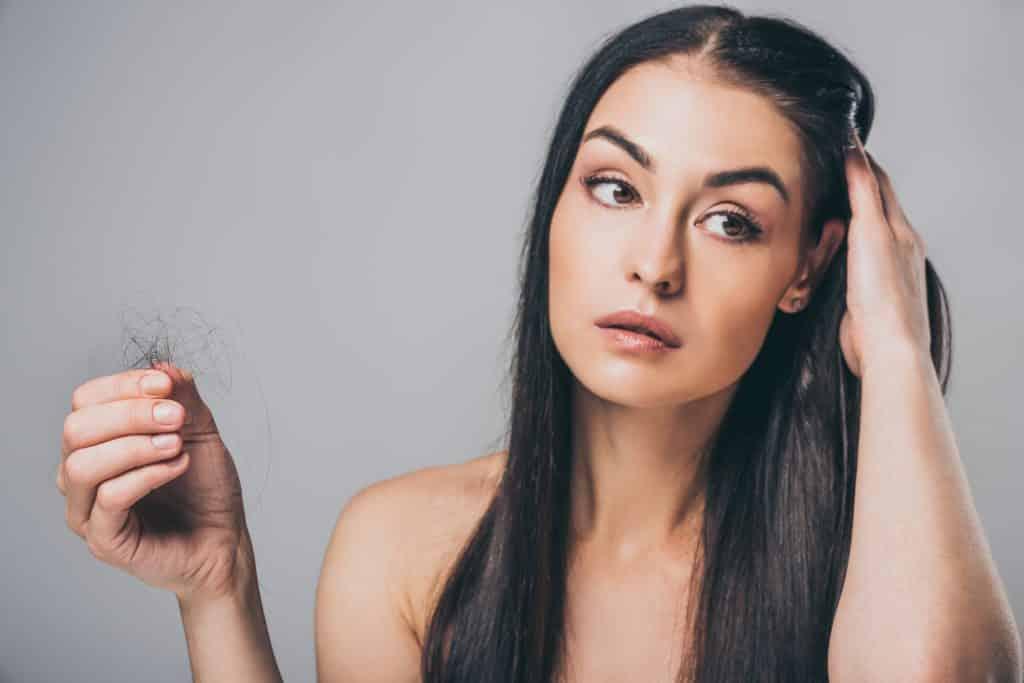Imagem de uma mulher de cabelos longos. Uma das suas mãos está sobre a cabeça e a outra segurando um monte de fios de cabelo que acabaram de cair.