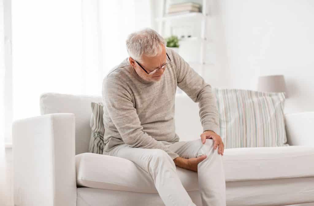 Idoso branco com dor no joelho.