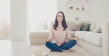 Mulher branca meditando no chão de uma sala.