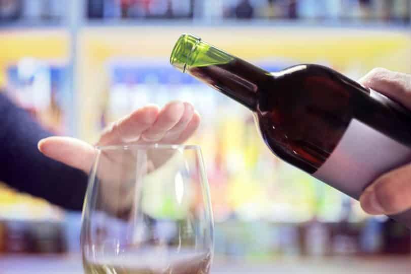 Mãos rejeitam vinho a ser derramado em taça.