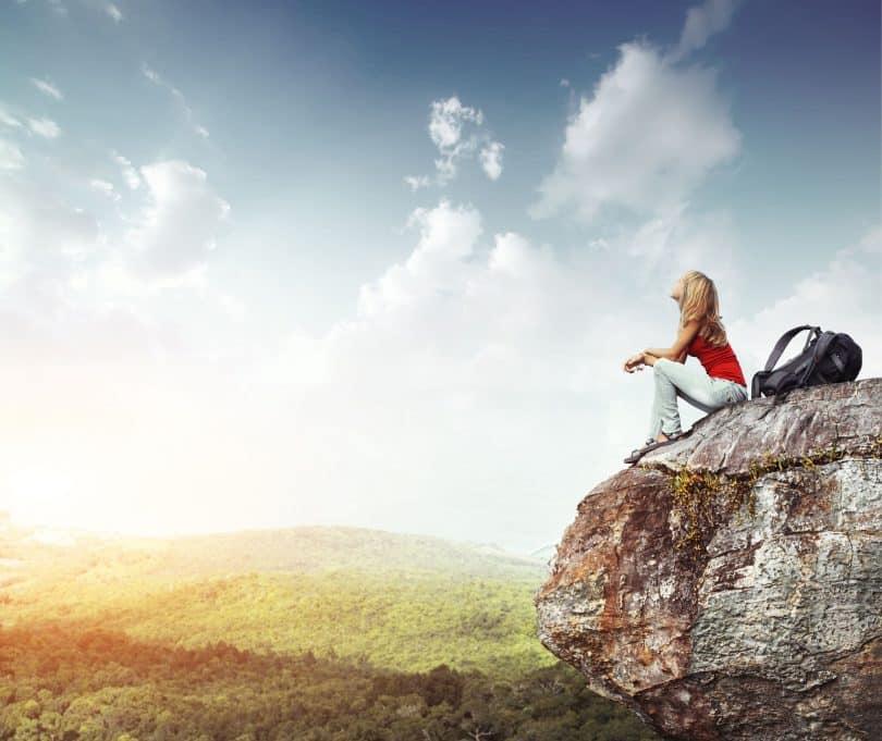 Mulher sentada em pico de montanha olha para cima.